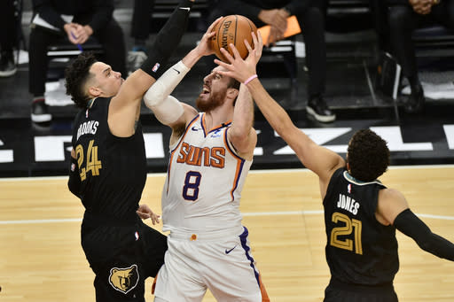 Phoenix Suns forward Frank Kaminsky (8) shoots against Memphis Grizzlies guards Dillon Brooks (24) and Tyus Jones (21) in the second half of an NBA basketball game Monday, Jan. 18, 2021, in Memphis, Tenn. (AP Photo/Brandon Dill)
