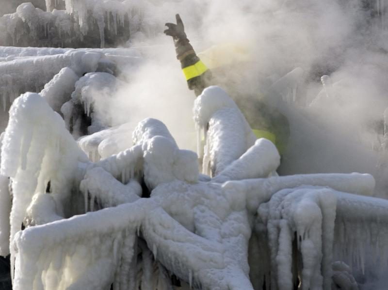 A police investigator, enveloped in steam, signals to colleagues as they search through the icy rubble of a fire that destroyed a seniors' residence Friday, Jan. 24, 2014, in L'Isle-Verte, Quebec. Five people are confirmed dead and 30 people are still missing, while with cause of Thursday morning's blaze is unclear police said. Authorities are using steam to melt the ice and to preserve any bodies that are buried. (AP Photo/The Canadian Press, Ryan Remiorz)