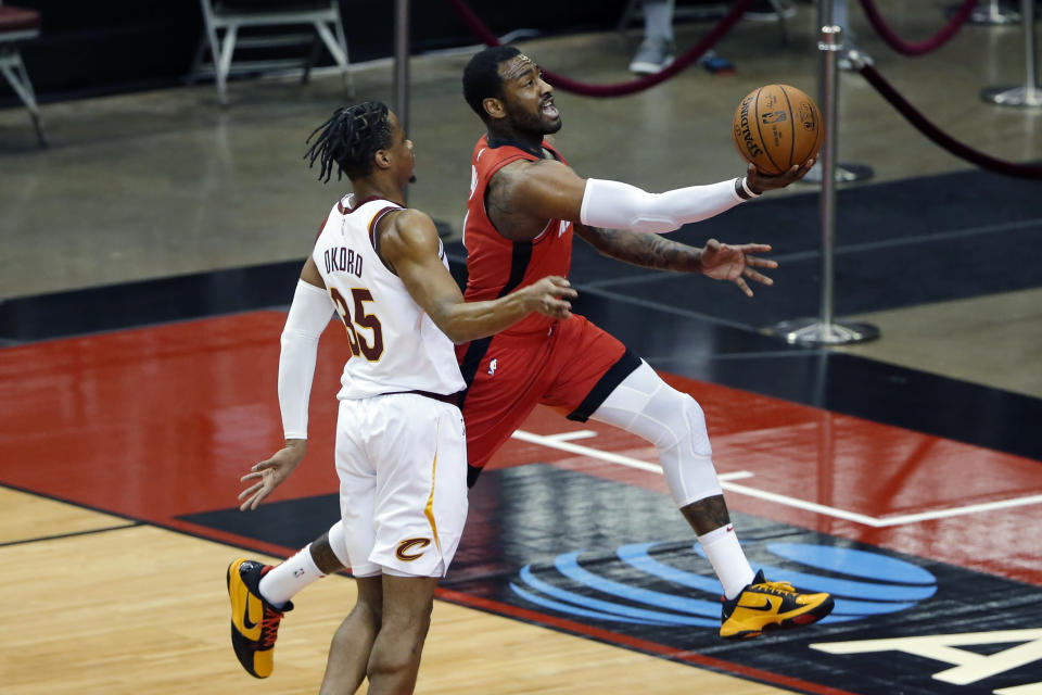 Houston Rockets guard John Wall, right, puts up a shot past Cleveland Cavaliers guard Isaac Okoro (35) during the first half of an NBA basketball game Monday, March 1, 2021, in Houston. (AP Photo/Michael Wyke)