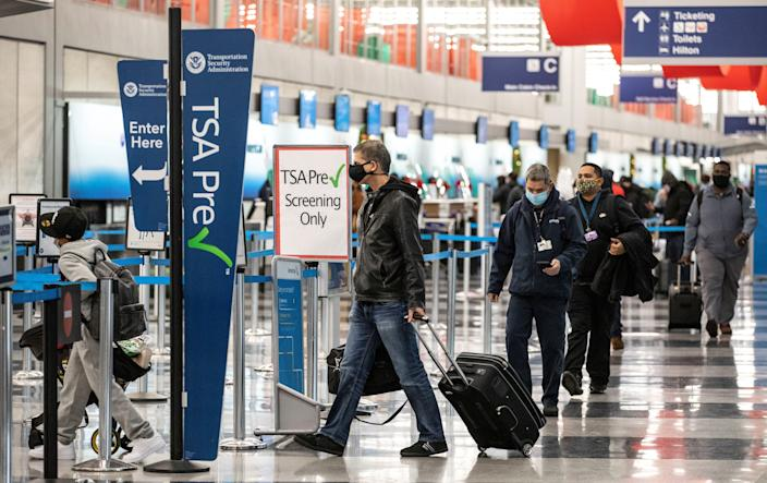 Travelers wearing face masks line up for security checks at O'Hare International Airport in Chicago, the United States, on Nov. 25, 2020. (Joel Lerner/Xinhua via Getty Images)