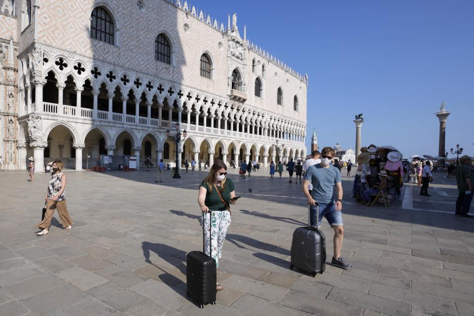Tourists walk with luggage across St. Mark's square, in Venice, Italy, Thursday, June 17, 2021. After a 15-month pause in mass international travel, Venetians are contemplating how to welcome visitors back to the picture-postcard canals and Byzantine backdrops without suffering the indignities of crowds clogging its narrow alleyways, day-trippers perched on stoops to imbibe a panino and hordes of selfie-takers straining for a spot on the Rialto Bridge or in front of St. Mark's Basilica. (AP Photo/Luca Bruno)