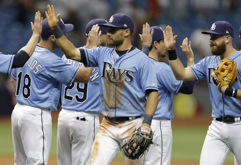 Tampa Bay Rays' Kevin Kiermaier, left, and third baseman Evan Longoria high-five teammates after the team defeated the New York Yankees in a baseball game Sunday, April 2, 2017, in St. Petersburg, Fla. (AP Photo/Chris O'Meara)