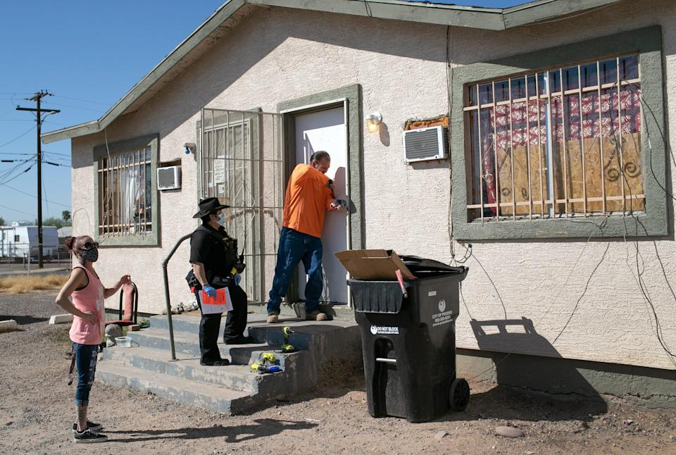 A maintenance man breaks the lock of a house as Maricopa County constable Darlene Martinez serves an eviction order on Oct. 1, 2020, in Phoenix.