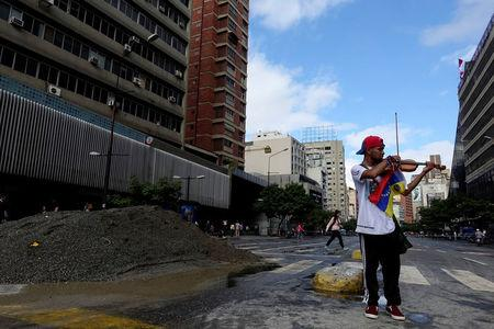 FILE PHOTO - Venezuelan violinist Wuilly Arteaga plays the violin next to a pile of sand used by protesters to block the street during a protest against Venezuelan President Nicolas Maduro's government in Caracas, Venezuela July 18, 2017. REUTERS/Carlos Garcia Rawlins