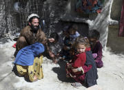 Internally displaced tribal leader Dawlat Khan plays with children and nephews in a house provided to him by relatives on the outskirts of Jalalabad, Afghanistan, Wednesday, April 21, 2021. Khan fled his village of Pananzai with his six brothers and their families at the height of the battles against the Islamic State terror network. They're not rushing home, even though the family of 63 people is crammed into nine small rooms. (AP Photo/Rahmat Gul)