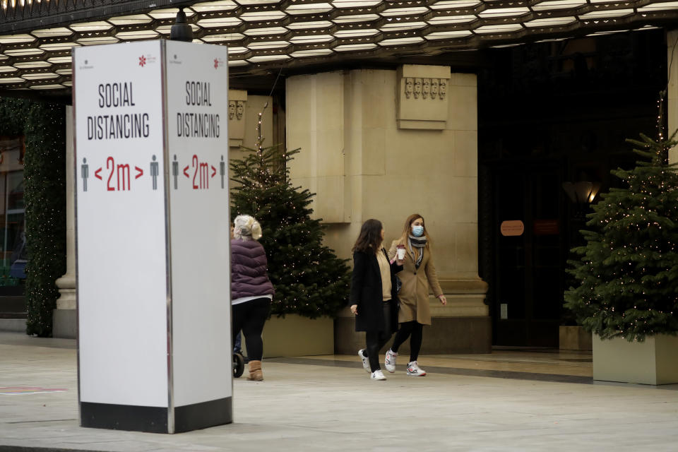 A woman wearing a face mask walks past Christmas trees and a social distancing sign outside the Selfridges department store on Oxford Street, which is temporarily closed for in-store browsing with online collection possible from a collection point, during England's second coronavirus lockdown, in London, Monday, Nov. 23, 2020. British Prime Minister Boris Johnson has announced plans for strict regional measures to combat COVID-19 after England's second lockdown ends Dec. 2, sparking a rebellion by members of his own party who say the move may do more harm than good. (AP Photo/Matt Dunham)