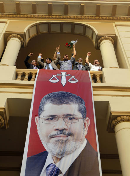 Egyptian campaign officials of the Muslim Brotherhood's candidate, Mohammed Morsi, celebrate over a giant poster of him at his campaign headquarters in Cairo, Egypt, Sunday, June 24, 2012. Mohammed Morsi was declared Egypt's first Islamist president on Sunday after the freest elections in the country's history, narrowly defeating Hosni Mubarak's last Prime Minister Ahmed Shafiq in a race that raised political tensions in Egypt to a fever pitch.(AP Photo/Amr Nabil)
