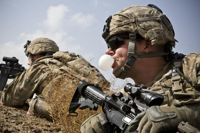 <p>A U.S. Army soldier with Charlie Company, 36th Infantry Regiment, 1st Armored Division blows a bubble with his chewing gum during a mission near Command Outpost Pa'in Kalay in Maiwand District, Kandahar Province Feb. 3, 2013. (Photo: Andrew Burton/Reuters) </p>