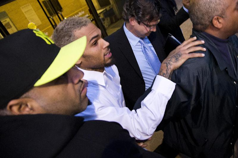 Singer Chris Brown is surrounded by bodyguards as he departs the H. Carl Moultriel courthouse Monday, Oct. 28, 2013, with one of his attorney's, Danny Onorato, second from right, in Washington. A charge against the Grammy Award-winning R&B singer has been reduced to a misdemeanor and he was ordered released after his arrest Sunday following an altercation outside a Washington hotel. (AP Photo/ Evan Vucci)
