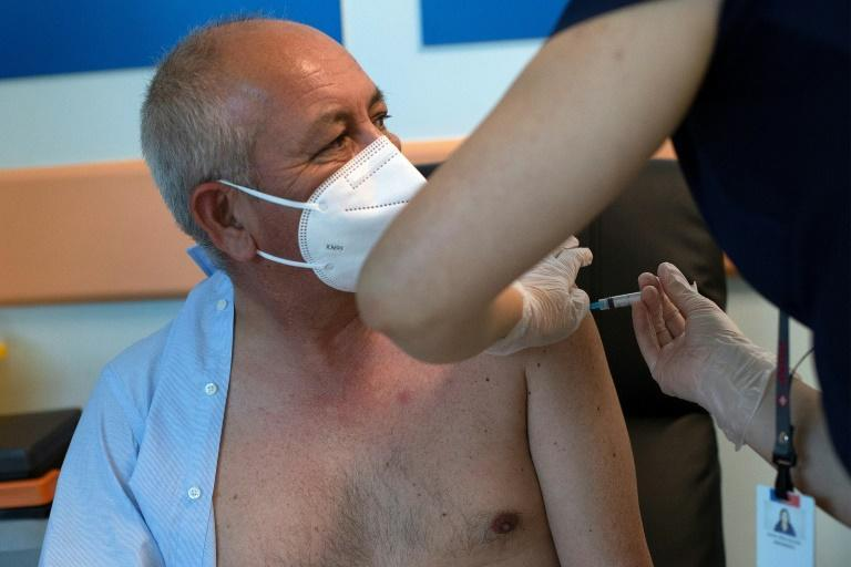 A medical worker receives the Pfizer/BioNTech Covid-19 vaccine jab at Hospital Posta Central in Santiago, on December 24, 2020