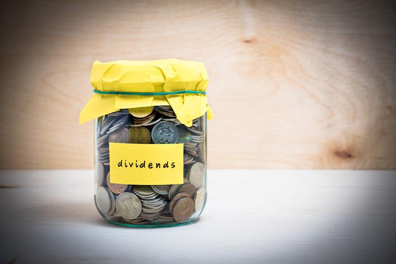 """A jar with a yellow cover marked """"dividends"""" and filled with coins sits on a table."""