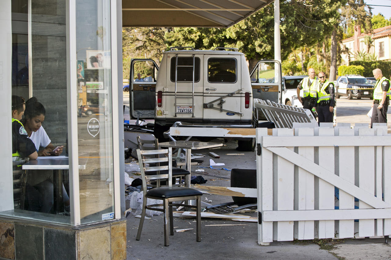 <p>A Los Angeles police investigator interviews a witness, at left, after a van plowed into a group of people on a Los Angeles sidewalk on Sunday, July 30, 2017. A witness to the crash told The Associated Press the van jumped a curb and careened into a group of people eating outside The Fish Spot restaurant in the city's Mid-Wilshire neighborhood. The cause of the crash is under investigation. (AP Photo/Damian Dovarganes) </p>