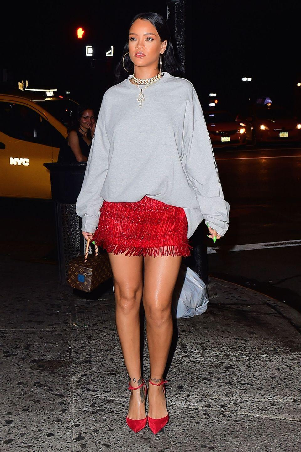 <p>In a grey sweatshirt, red fringed skirt, gold hoop earrings and chain necklace, red pointed-toe ankle strap heels and a Louis Vuitton bag while out in NYC. </p>