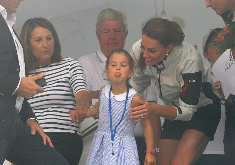 Princess Charlotte, flanked by her grandmother and mother, gestures through a window at the prize giving after the King's Cup regatta. (Photo: PA Wire/PA Images)
