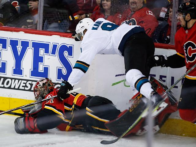San Jose Sharks left wing Evander Kane (9) knocks Calgary Flames goaltender Mike Smith (41) to the ice during the first period of an NHL hockey game Friday, March 16, 2018, in Calgary, Alberta. (Jeff McIntosh/The Canadian Press via AP)