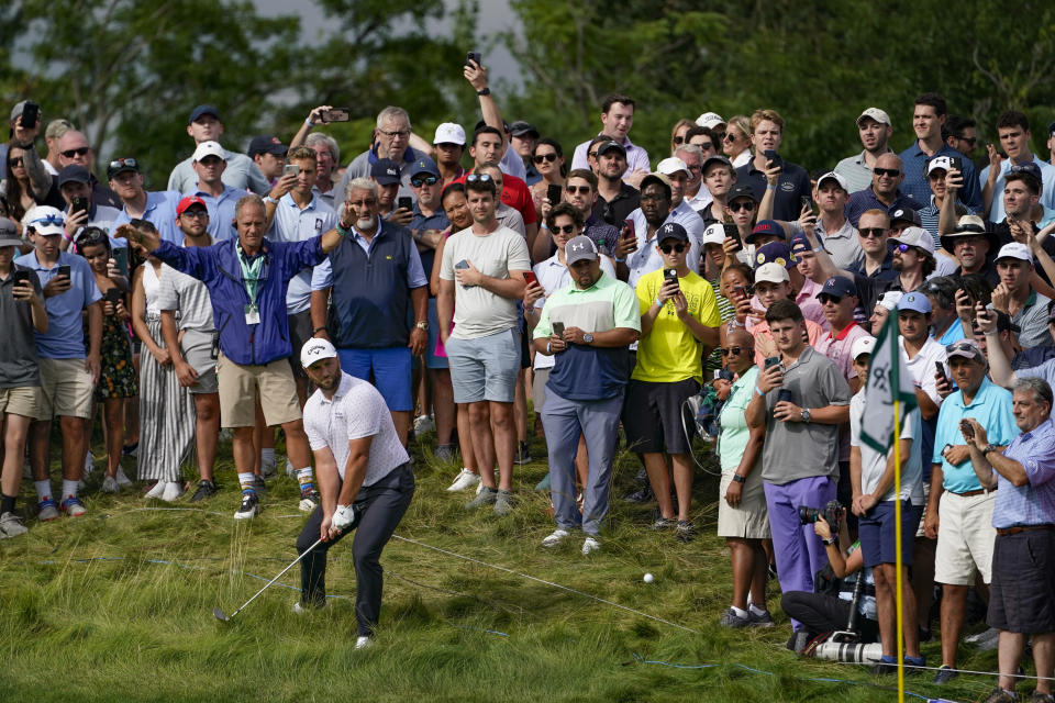 Jon Rahm, of Spain, hits from the rough onto the 13th green amongst spectators in the third round at the Northern Trust golf tournament, Saturday, Aug. 21, 2021, at Liberty National Golf Course in Jersey City, N.J. (AP Photo/John Minchillo)