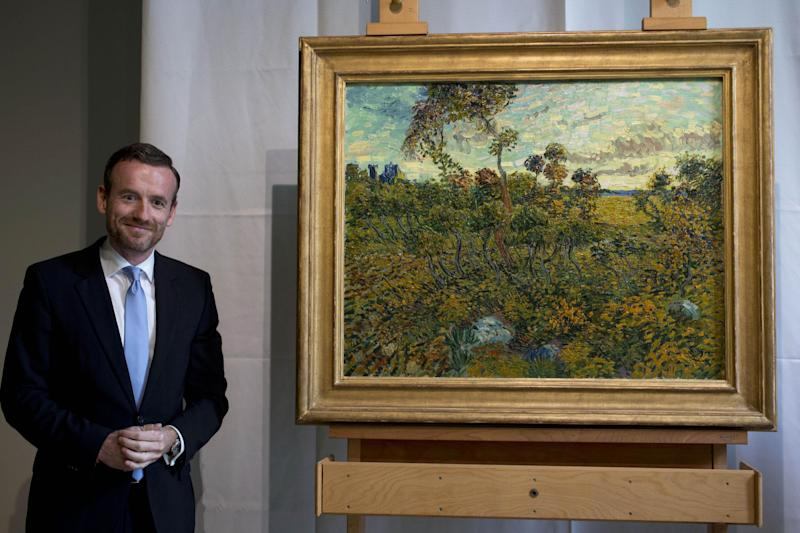 """CAPTION CORRECTION, CORRECTS SPELLING OF SURNAME TO REFLECT AP STYLE - Van Gogh Museum director Axel Rueger, left, poses next to """"Sunset at Montmajour"""" after unveiling the painting by Dutch painter Vincent van Gogh during a press conference at the museum in Amsterdam, Netherlands, Monday Sept. 9, 2013. The museum has identified the long-lost painting which was painted by the Dutch mater in 1888, the discovery is the first full size canvas that has been found since 1928 and will be on display from Sept. 24. (AP Photo/Peter Dejong)"""