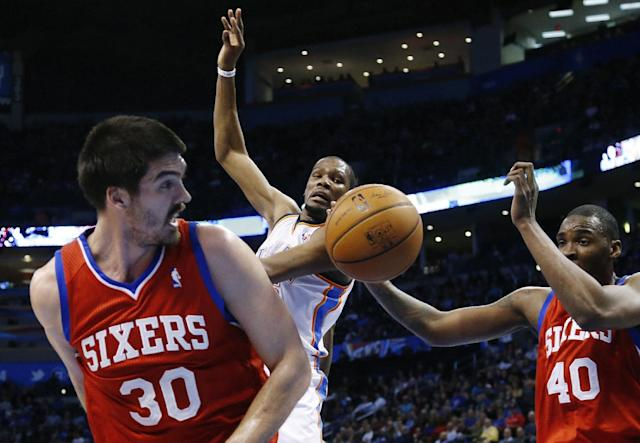 Oklahoma City Thunder forward Kevin Durant (35) loses the ball after a foul by Philadelphia 76ers center Byron Mullens (30) during the third quarter of an NBA basketball game in Oklahoma City, Tuesday, March 4, 2014. 76ers forward Jarvis Varnado is at right. Oklahoma City won 125-92. (AP Photo/Sue Ogrocki)
