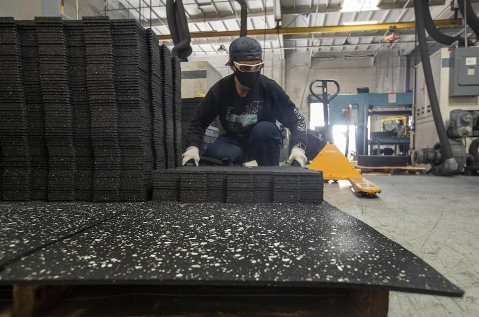 Alisha Kerichenko, 45, stacks rubber tiles after dye cutting them at U.S. Rubber Recycling in Colton.