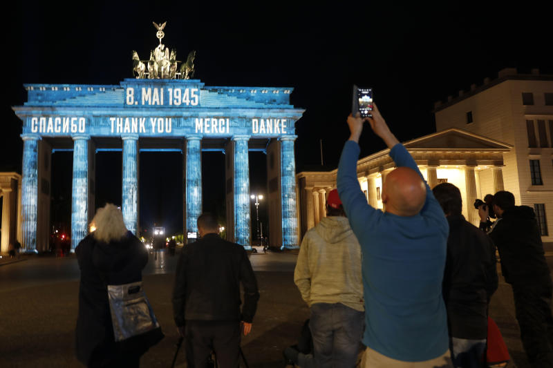"""People make pictures from Germany's landmark Brandenburg Gate, illuminated to mark the 75th anniversary of Victory Day and the end of World War II in Europe, in Berlin, Germany, Friday, May 8, 2020. With the projection of the word """"Thank You"""" in various languages Berlin commemorates the liberation of Germany by the allied forces in 1945. (AP Photo/Markus Schreiber)"""
