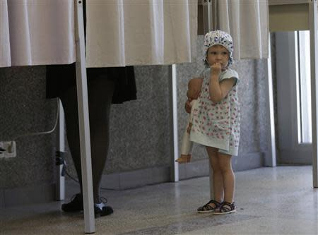 A girl holding a doll waits for her mother outside a voting booth during European Parliament and Lithuania's presidential elections in Vilnius May 25, 2014. REUTERS/Ints Kalnins