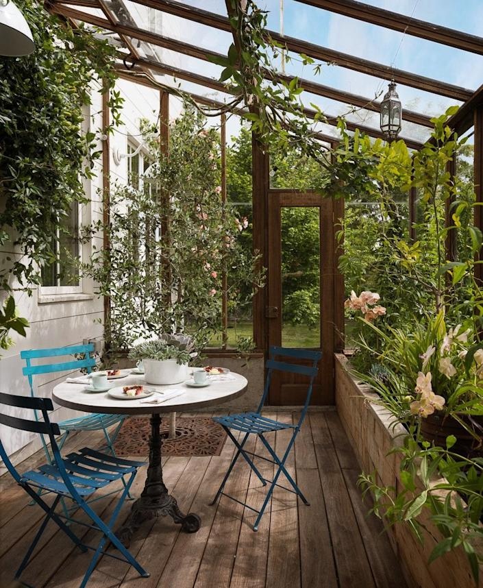 The charming greenhouse has passion vine, star jasmine, and a zellige tabletop with vintage cast-iron base.