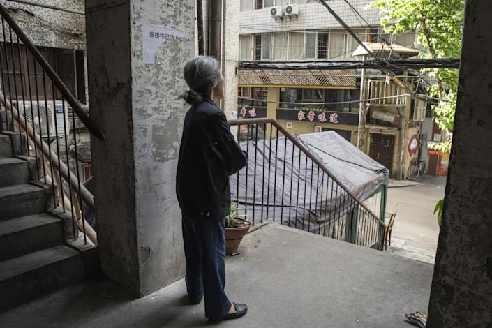 """A woman in Wuhan stands just outside her apartment in May 2020. Residents feared new limits on movement. <span class=""""copyright"""">(For The Times)</span>"""