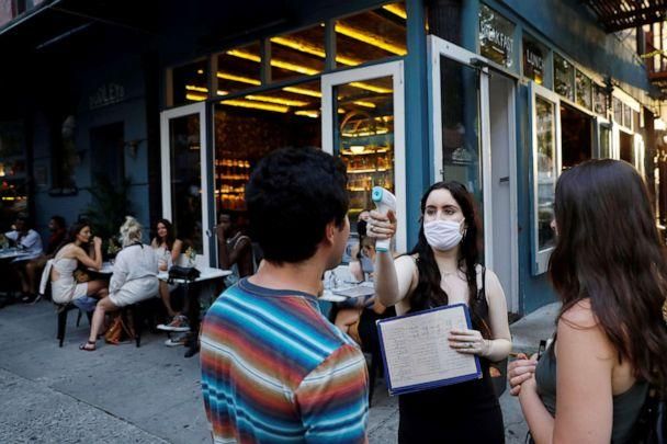 PHOTO: A waitress takes the temperature of customers at Dudley's as restaurants are permitted to offer al fresco dining as part of phase 2 reopening during the coronavirus pandemic in the Lower East Side of Manhattan in New York City, June 27, 2020. (Andrew Kelly/Reuters)
