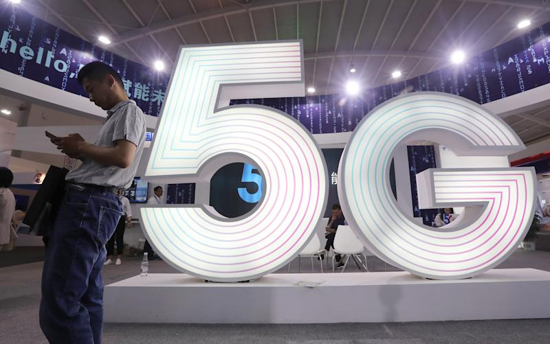 A man stands next to a sign of 5G at the Tencent Global Digital Ecosystem Summit in Kunming, Yunnan province, China May 23, 2019. Picture taken May 23, 2019. REUTERS/Stringer ATTENTION EDITORS - THIS IMAGE WAS PROVIDED BY A THIRD PARTY. CHINA OUT.