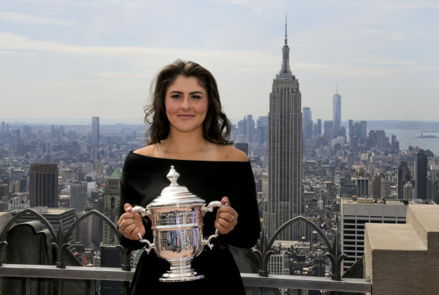 FILE - In this Sept. 8, 2019, file photo, Bianca Andreescu, of Canada, poses with the U.S. Open women's singles championship trophy at Top of the Rock in New York. New York Gov. Andrew Cuomo said Tuesday, June 16, 2020, that the U.S. Open tennis tournament will held starting in late August as part of the state's reopening from shutdowns caused by the coronavirus pandemic.(AP Photo/Charles Krupa, File)