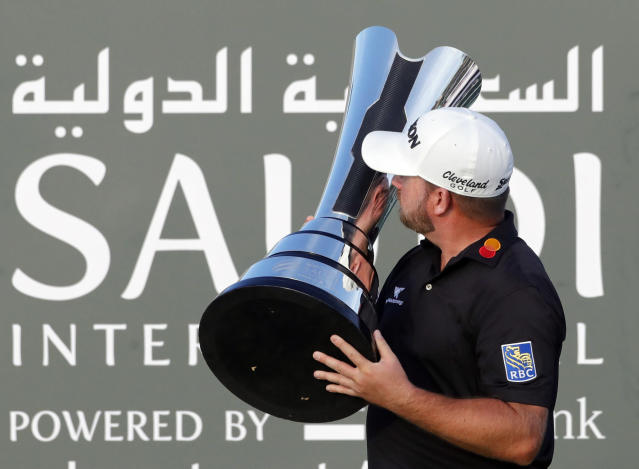 Graeme McDowell from Northern Ireland kiss the trophy after he wins the final round of the Saudi International at Royal Greens Golf and Country Club, Sunday, Feb. 2, 2020, in Red Sea resort of King Abdullah Economic City, Saudi Arabia. (AP Photo/Amr Nabil)