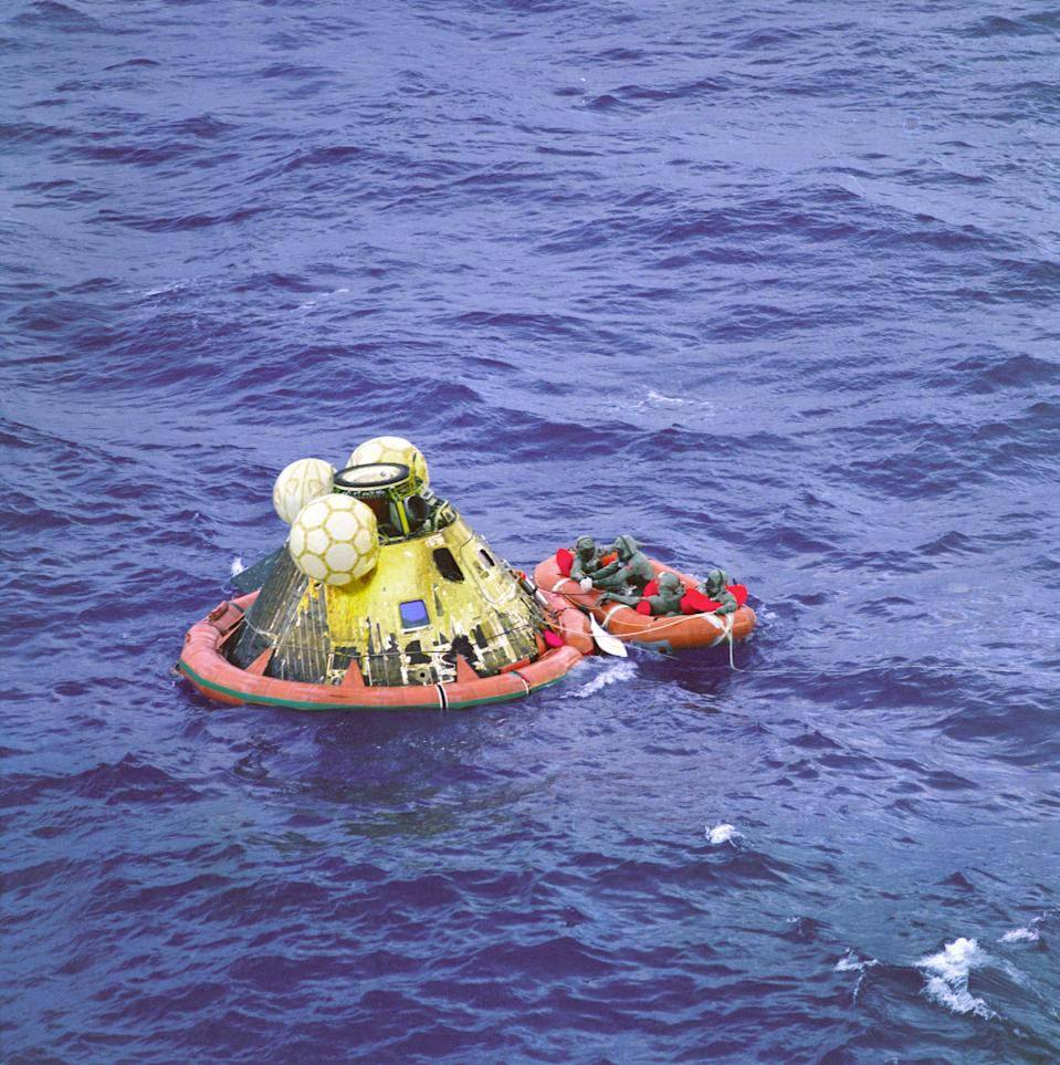 """The Apollo 11 crew await pickup by a helicopter from the USS Hornet, prime recovery ship for the historic Apollo 11 lunar landing mission. The fourth man in the life raft is a United States Navy underwater demolition team swimmer. All four men are wearing Biological Isolation Garments (BIG). The Apollo 11 Command Module """"Columbia,"""" with astronauts Neil A. Armstrong, Michael Collins, and Edwin E. Aldrin Jr. splashed down at 11:49 a.m. (CDT), July 24, 1969, about 812 nautical miles southwest of Hawaii and only 12 nautical miles from the USS Hornet. (Photo: NASA)"""