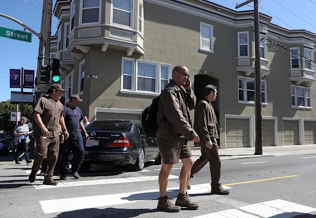 <p>UPS workers are escorted by San Francisco police at the scene of a shooting at a UPS facility on June 14, 2017 in San Francisco, California. (Justin Sullivan/Getty Images) </p>