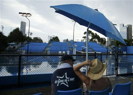 Spectators wait for a storm to pass before play on courts outside start again at the Australian Open 2014 tennis tournament in Melbourne January 16, 2014. REUTERS/Jason Reed