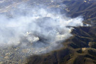 Smoke rises from the site of a wildfire in Ashikaga, Tochigi prefecture, north of Tokyo Wednesday, Feb. 24, 2021. A forest fire broke out in the rural area Thursday, near another blaze burning since Sunday, Feb. 21. (Kyodo News via AP) (Kyodo News via AP)