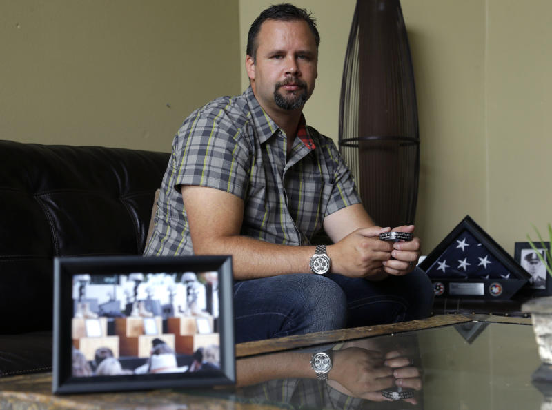 FILE - In this Aug. 3, 2013 file photo, retired U.S. Army Staff Sgt. Shawn Manning poses for a photo at his home in Lacey, Wash., as he holds a photograph from the memorial for victims of the 2009 mass shooting at Fort Hood, Texas. Manning, who still carries two bullets in his body from the shooting that killed 13 people, estimates he has lost $2,000 a month in pay and benefits because of the decision to classify the injuries as resulting from workplace violence rather than combat or terrorist-related. Had his injuries been classified as terrorist-related, the military would have paid the difference between his civilian and reserve salary, offered him better medical benefits and granted him greater disability payments. (AP Photo/Ted S. Warren, File)