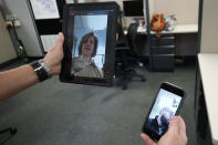 In this Friday, Aug. 13, 2021, photo Sheriff's Police Sgt. Bonnie Busching tests a virtual meeting from her tablet to her teammate cellphone at the Cook County Sheriff's Office in Chicago. The Cook County Sheriff's department officers are hitting the streets with tablets that can connect people in distress immediately with mental health professionals. And Cook County Sheriff Tom Dart says the Treatment Response Team has been successful bringing calm to the tensest of domestic situations involving people at risk of hurting themselves or others. (AP Photo/Nam Y. Huh)