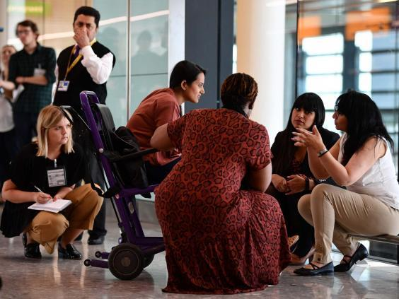A family is asked questions by officials after landing from Bangalore in India, in Terminal 2 at Heathrow Airport in London on 16 July, as part of Operation Limelight (AFP/Getty)