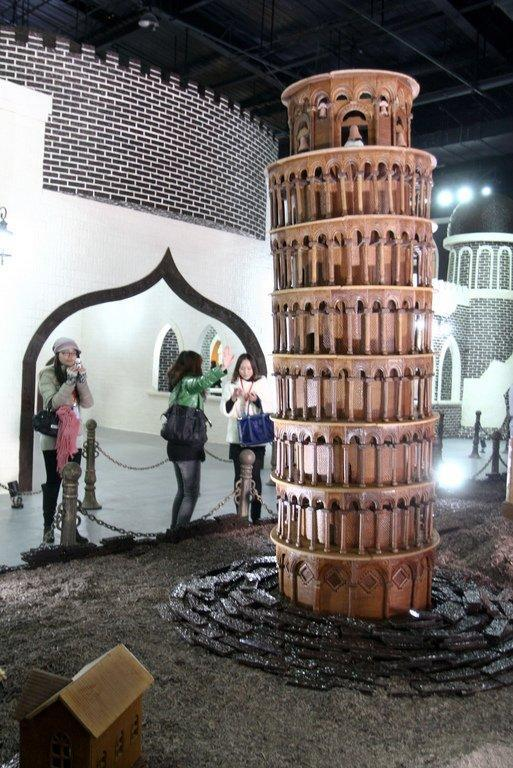 Visitors snap photos on January 18, 2013 of a chocolate Leaning Tower of Pisa, at the Chocolate Happy Land, in Shanghai. China's increasingly wealthy shoppers have enthusiastically embraced global trends from coffee to Hollywood films to smartphones, and become the world's largest market for goods from beer to cars