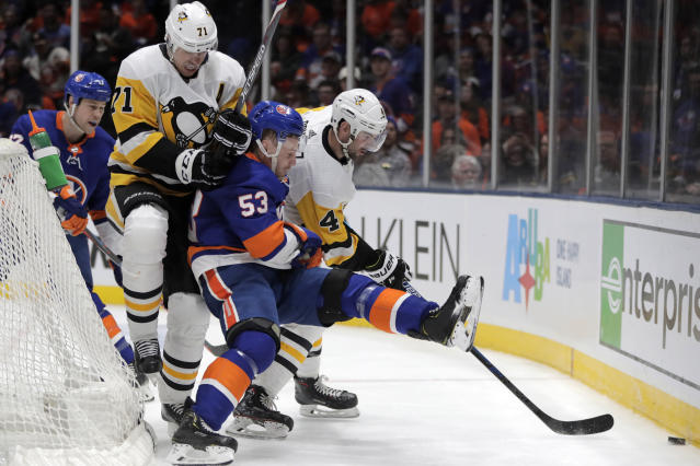 New York Islanders center Casey Cizikas (53) is sandwiched between Pittsburgh Penguins center Evgeni Malkin (71), of Russia, and defenseman Justin Schultz (4) while competing for possession of the puck during the second period of Game 2 of an NHL hockey first-round playoff series Friday, April 12, 2019, in Uniondale, N.Y. (AP Photo/Julio Cortez)