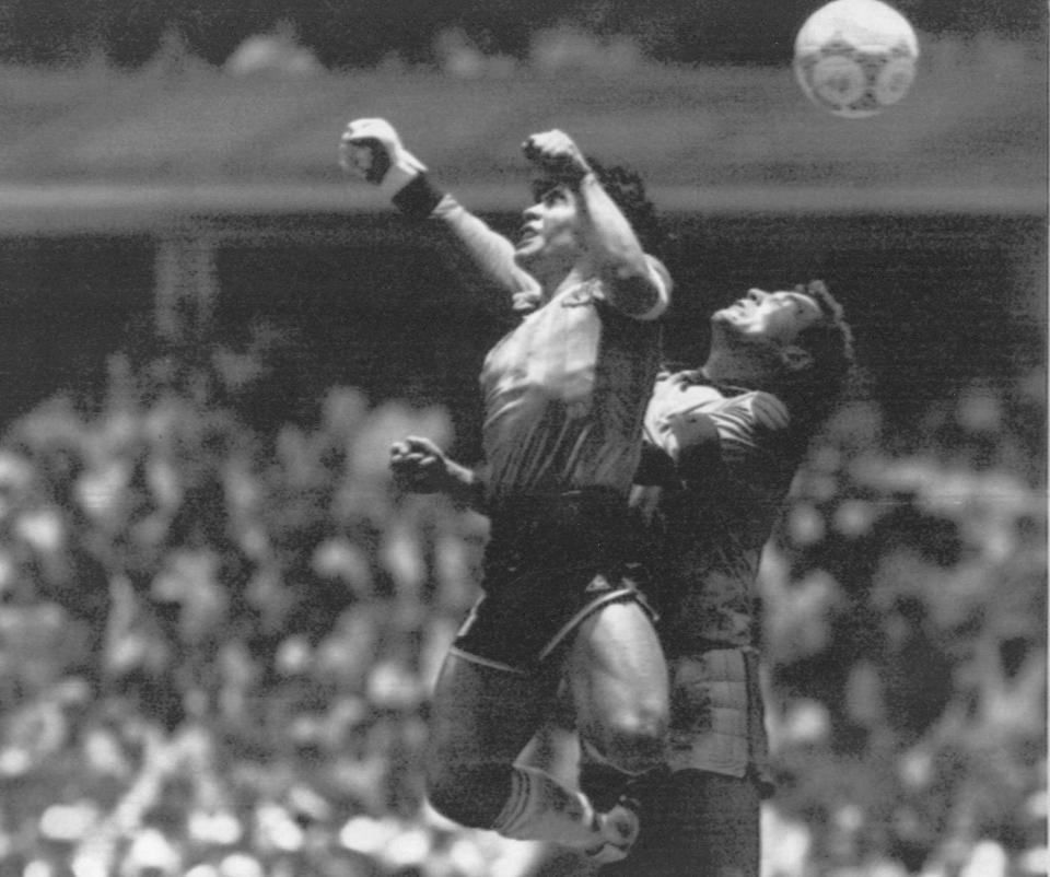 "FILE - In this June 22, 1986 file photo, Argentina's Diego Maradona, left, beats England's goalkeeper Peter Shilton to a high ball and scores his first of two goals at the World Cup quarterfinal soccer match in Mexico City. On this day: This was the day of the ""Hand of God,"" when Maradona used his left fist to knock a ball past England's Shilton. (El Grafico via AP, File)"