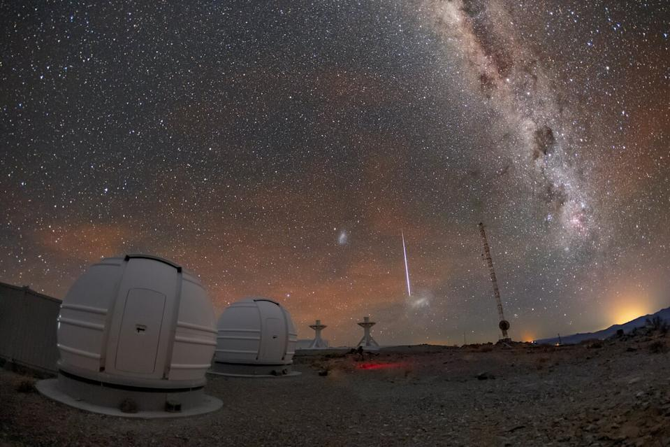 "A ""shooting star"" streaks through the night sky near the Large and Small Magellanic Clouds, two of Earth's galactic neighbors, in this photo from the La Silla Observatory in Chile. In the foreground of the image are two of the three new ExTrA (Exoplanets in Transits and their Atmospheres) telescopes at the observatory."