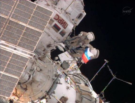 A cosmonaut unfurls a Russian flag outside the International Space Station during a spacewalk on Aug. 22, 2013, to mark Russian Flag Day.