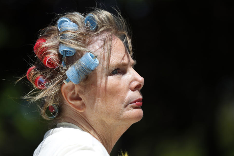 Carolyn Kirin wears curlers in her hair at a rally giving free haircuts at the State Capitol in Lansing, Mich., Wednesday, May 20, 2020. Barbers and hair stylists are protesting the state's stay-at-home orders, a defiant demonstration that reflects how salons have become a symbol for small businesses that are eager to reopen two months after the COVID-19 pandemic began. (AP Photo/Paul Sancya)