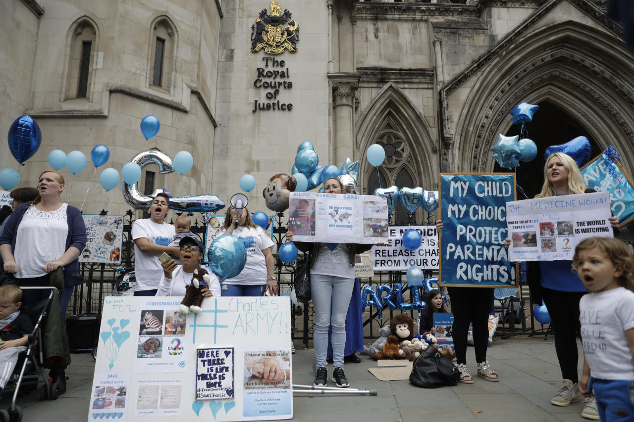 Supporters of critically ill baby Charlie Gard shout and hold placards before his parents Connie Yates and Chris Gard arrived at the High Court in London, Monday, July 24, 2017. The parents of the 11-month old, who has a rare genetic condition and brain damage, are returning to court for the latest stage in their effort to seek permission to take the child to the United States for medical treatment. (AP Photo/Matt Dunham)