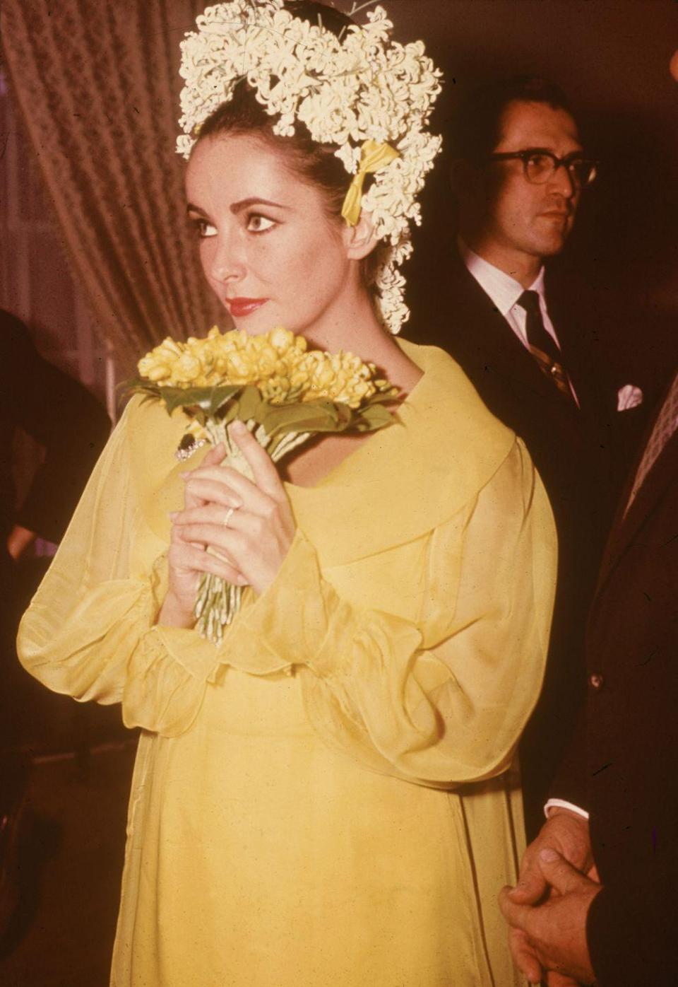 <p>For her wedding to fifth husband Richard Burton, Taylor opted for a canary yellow chiffon dress topped off with dozens of white flowers in her hair. While her penchant for getting married certainly made the news more than her gowns, this was her brightest dress to date.</p>