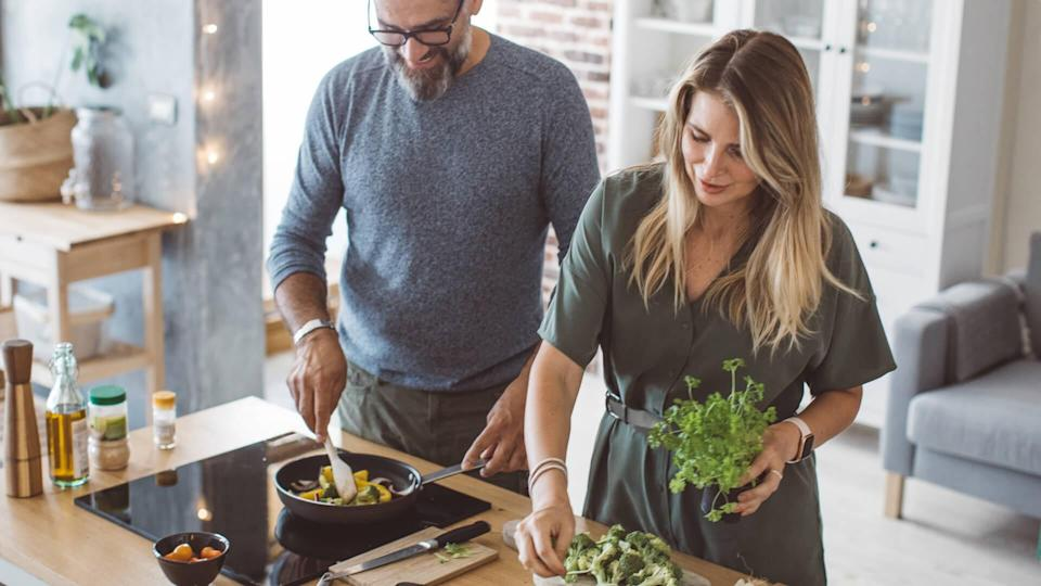 Man and woman preparing delicious vegetable meal, everything is so green, healthy and freshly harvested from garden.