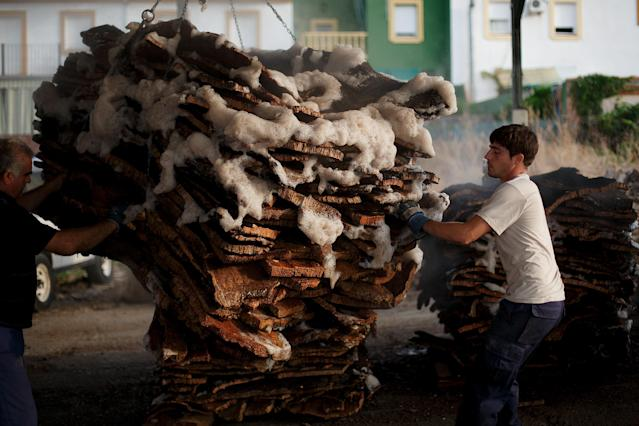 EL PEDROSO, SPAIN - JULY 02: (L-R) Jesus Rios Nogales, 49, and Ezequiel Rodriguez, 21, take out a pile of cork planks from boiling at a factory on July 2, 2013 in El Pedroso, near Seville, Spain. A factory in El Pedroso processes raw cork planks through traditional methods. The bark from the oak is harvested every nine years, through traditional methods. The best planks are sourced for wine bottling corks while the rest is processed into agglomerate cork. (Photo by Pablo Blazquez Dominguez/Getty Images)