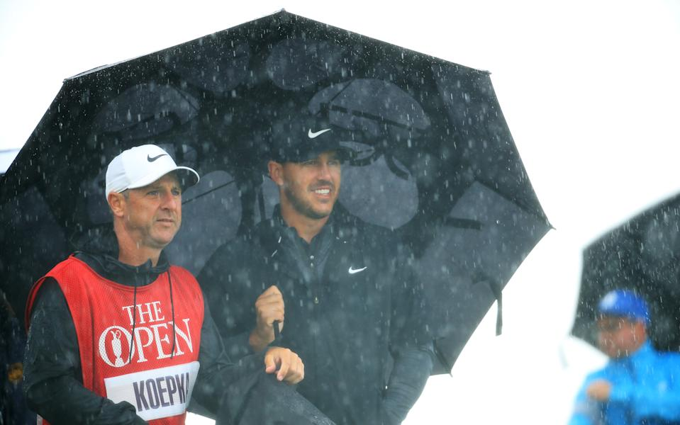 Brooks Koepka of the United States shelters under an umbrella with caddie, Ricky Elliot on the 3rd hole during the first round of the 148th Open Championship held on the Dunluce Links at Royal Portrush Golf Club on July 18, 2019 in Portrush, United Kingdom. (Photo by Andrew Redington/Getty Images)
