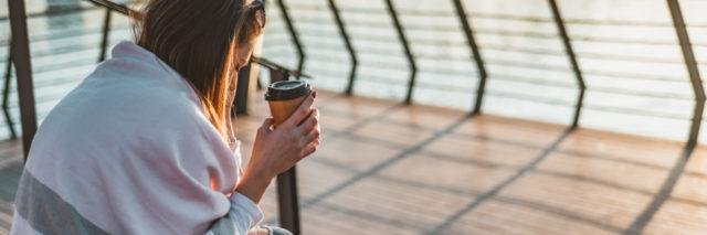 woman sitting with a cup of coffee near the water